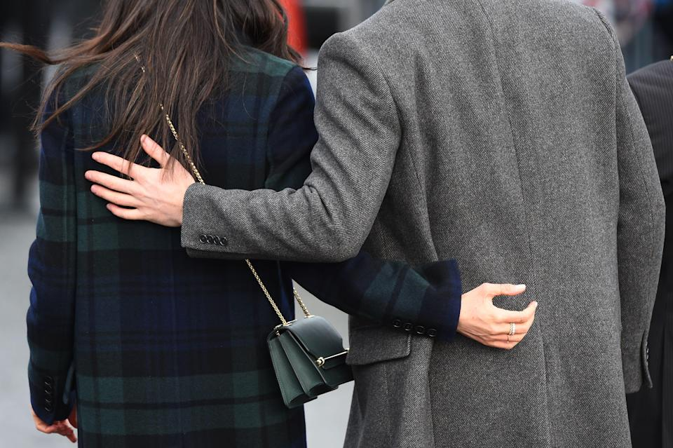 Prince Harry and Meghan Markle stand with their arms around each other.