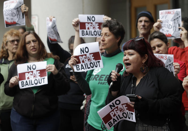FILE - In this Jan. 28, 2019, file photo, Jessica Tovar, right, speaks at a rally before a California Public Utilities Commission meeting in San Francisco. A state lawmaker is demanding an extensive review of the California Public Utilities Commission to determine whether regulators' lax oversight enabled the neglectful behavior at Pacific Gas & Electric that triggered catastrophic wildfires, a messy bankruptcy and exasperating blackouts. (AP Photo/Jeff Chiu, File)