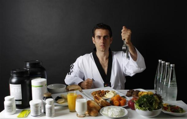 Turkish Taekwondo fighter and Olympic hopeful Bahri Tanrikulu, 32, poses in front of his daily meal intake in Ankara May 24, 2012.