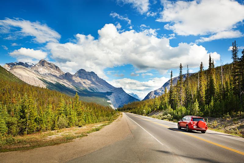 A car drives through Banff National Park in Alberta. (Photo: YinYang via Getty Images)