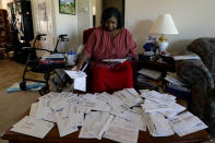 Debra Smith, 57, sorts through her medical bills in her living room on Thursday, Oct. 7, 2021, in Spring Hill, Tenn. Smith, who has health problems that prevent her from working, has about $10,000 in unpaid medical bills. Patient advocates and some state governments say hospitals must do more to help patients deal with medical bills before the debt winds up in collections. (AP Photo/Mark Zaleski)