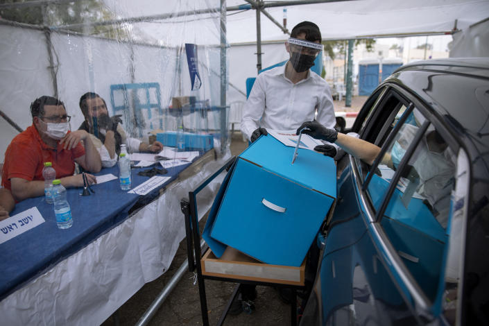 A women votes for Israel's parliamentary election at a special drive-in polling station for people who are in quarantine for coronavirus, in Ramat Gan, Israel, Tuesday, March. 23, 2021. Israel is holding its fourth election in less than two years. (AP Photo/Oded Balilty)