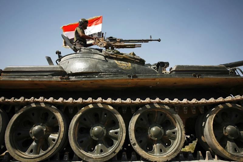 A member of the Popular Mobilisation Units supporting the government forces drives a tank flying the Iraqi flag on the outskirts of Najaf (AFP Photo/Haidar HAMDANI)