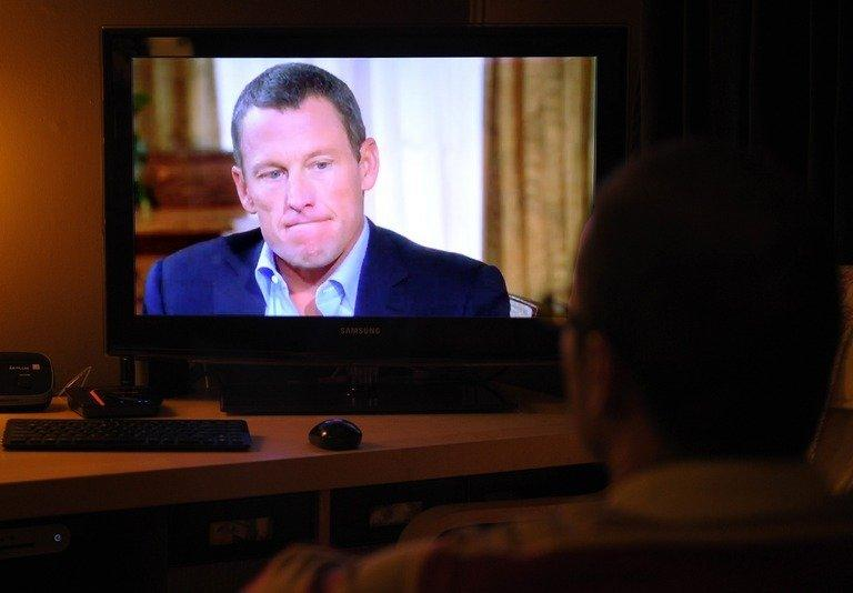 A man watches disgraced cycling star Lance Armstrong being interviewed by Oprah Winfrey on January 17, 2013