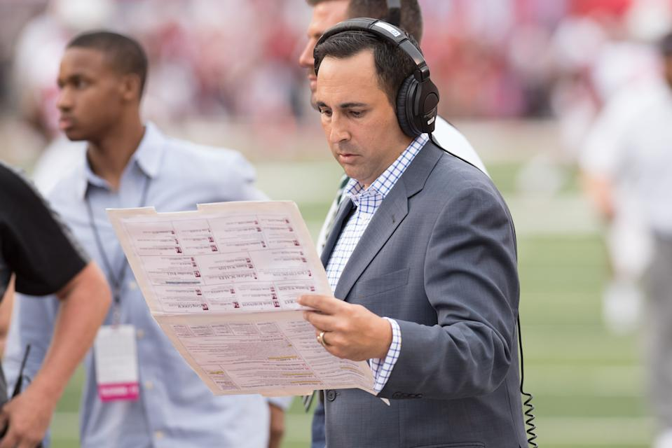 Joe Tessitore looks over his announcer's sheet with a headset on.