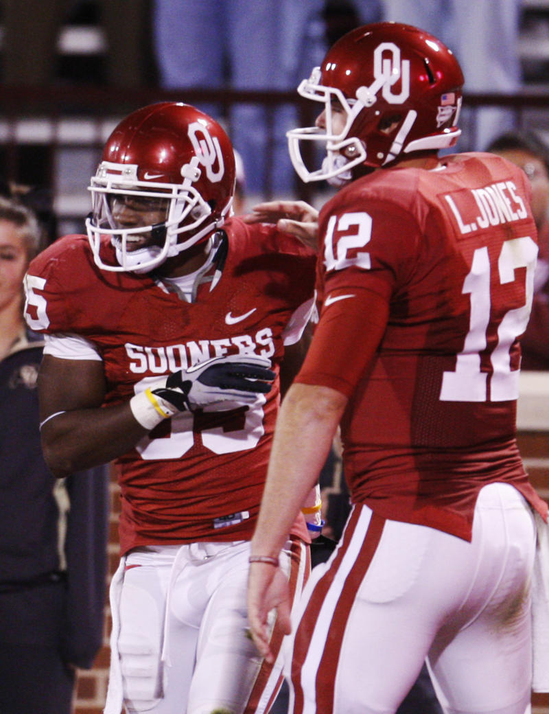 Oklahoma wide receiver Ryan Broyles, left, is congratulated by quarterback Landry Jones, right, following his touchdown against Colorado in the third quarter of an NCAA college football game in Norman, Okla., Saturday, Oct. 30, 2010. (AP Photo/Sue Ogrocki)