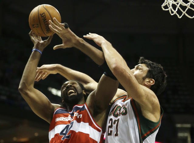Washington Wizards' Nene Hilario, left, is fouled as he tries to shoot past Milwaukee Bucks' Zaza Pachulia (27) during the first half of an NBA basketball game Wednesday, Nov. 27, 2013, in Milwaukee. (AP Photo/Morry Gash)