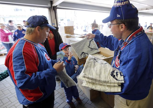 Usher John O'Brien, right, hands out the 1914 replica Chicago Federals' jersey to fans for the 100th anniversary of the first baseball game at Wrigley Field, before a game between the Arizona Diamondbacks and Chicago Cubs, Wednesday, April 23, 2014, in Chicago. (AP Photo/Charles Rex Arbogast)