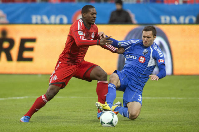 Toronto FC 's Doneil Henry, left, battles for the ball with Montreal Impact's Andrew Wenger during the first half of an MLS soccer game in Toronto, Saturday, Oct. 26, 2013. (AP Photo/The Canadian Press, Chris Young)