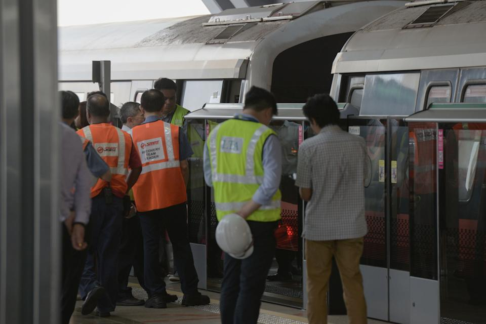 Staff from SMRT and Singapore's Land Transport Authority gather around two trains that collided at a train station in Singapore on November 15, 2017. At least 25 people were injured in a train collision in Singapore on November 15, officials said, in the latest incident to hit the troubled metro system. / AFP PHOTO / TOH Ting Wei        (Photo credit should read TOH TING WEI/AFP/Getty Images)