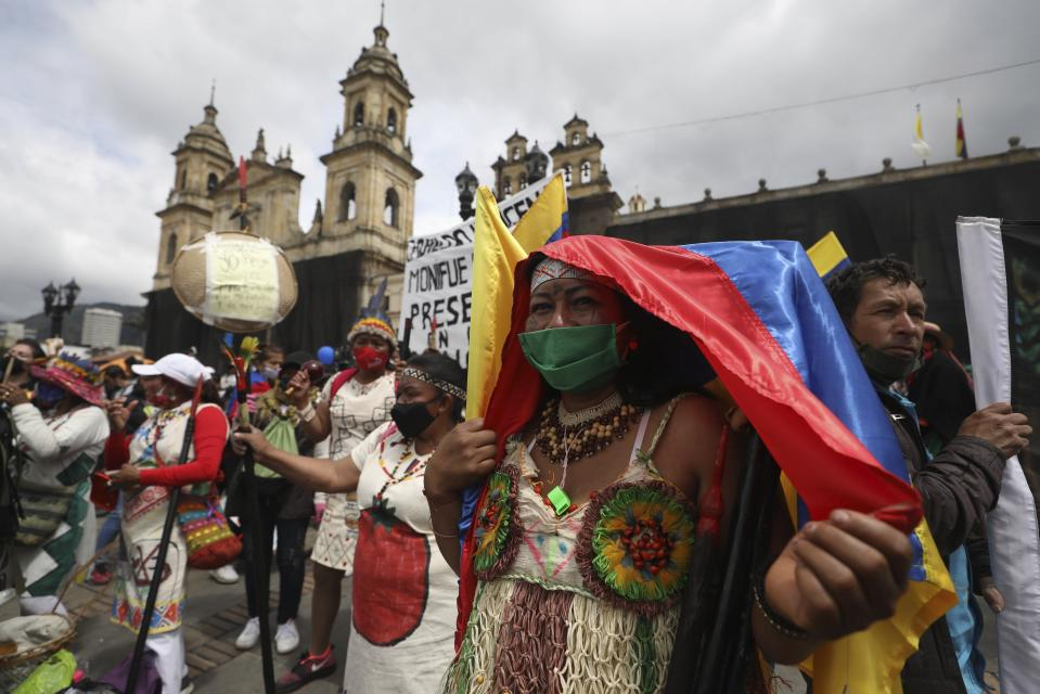 Protesters gather in Plaza Bolivar to demonstrate against the government's handling of a wide range of issues including the economic fallout of the pandemic and implementation of the peace accord, as part of a national strike in Bogota, Colombia, Wednesday, Oct. 21, 2020. Indigenous leaders, students and union members gathered at in the historic square waving flags and banners decrying the government nearly one year after massive protests rocked the country only to fizzle with little to show by way of reform. (AP Photo/Fernando Vergara)