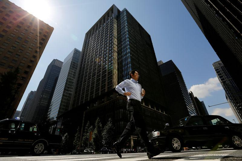 FILE PHOTO: A man runs on a crosswalk at a business district in central Tokyo