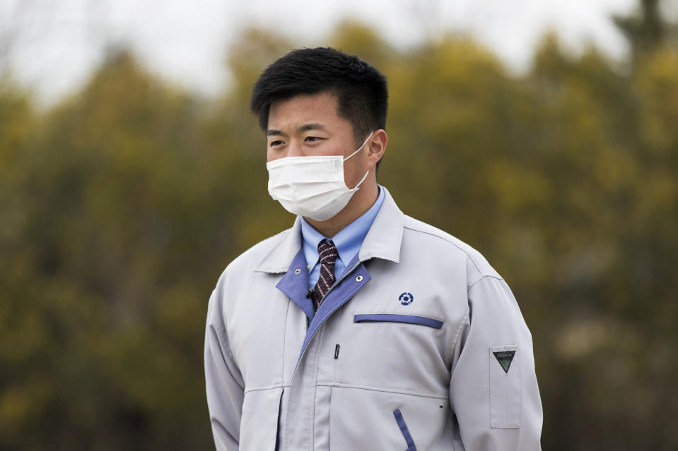 "Yuya Hatakeyama, a Tomioka town official, speaks during an interview with The Associated Press as he guides reporters in a ""difficult-to-return"" zone in Tomioka town, Fukushima prefecture, northeastern Japan, Friday, Feb. 26, 2021. Hatakeyama, forced to evacuate as a 14-year-old junior high school student, is back in town as a rookie official. Now at age 24, Hatakeyama wants to help rebuild the community and reconnect residents for the struggling town. (AP Photo/Hiro Komae)"
