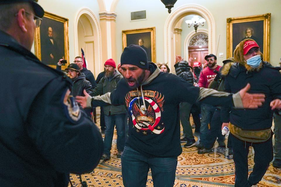 File: Trump supporters, including Doug Jensen, centre, confront US Capitol police in the hallway outside of the Senate chamber at the Capitol  (AP)