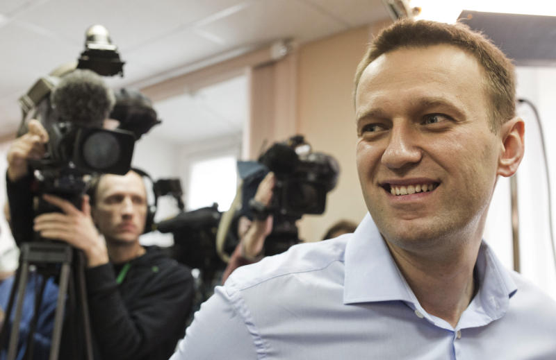 Russian opposition leader Alexei Navalny smiles in a courtroom as he attends a trial in Kirov, Russia, Wednesday, April 24, 2013. The trial has resumed in the case against a Russian opposition leader who led protests against President Vladimir Putin and exposed alleged corruption in his government.Navalny is accused of heading an organized criminal group that embezzled 16 million rubles ($500,000) worth of timber from a state-owned company. (AP Photo/Yevgeny Feldmany)