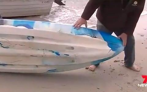 A man showing the marks left on the kayak after the attack  - Credit: 7 news