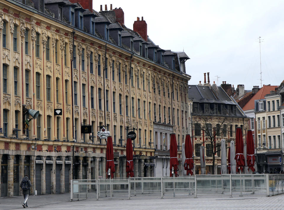 A man walks in the main square in Lille, northern France, Sunday March 15, 2020. French Prime Minister Edouard Philippe announced that France is shutting down all restaurants, cafes, cinemas and non-essential retail shops, starting Sunday, to combat the accelerated spread of the virus in the country. For most people, the new coronavirus causes only mild or moderate symptoms. For some it can cause more severe illness. (AP Photo/Michel Spingler)