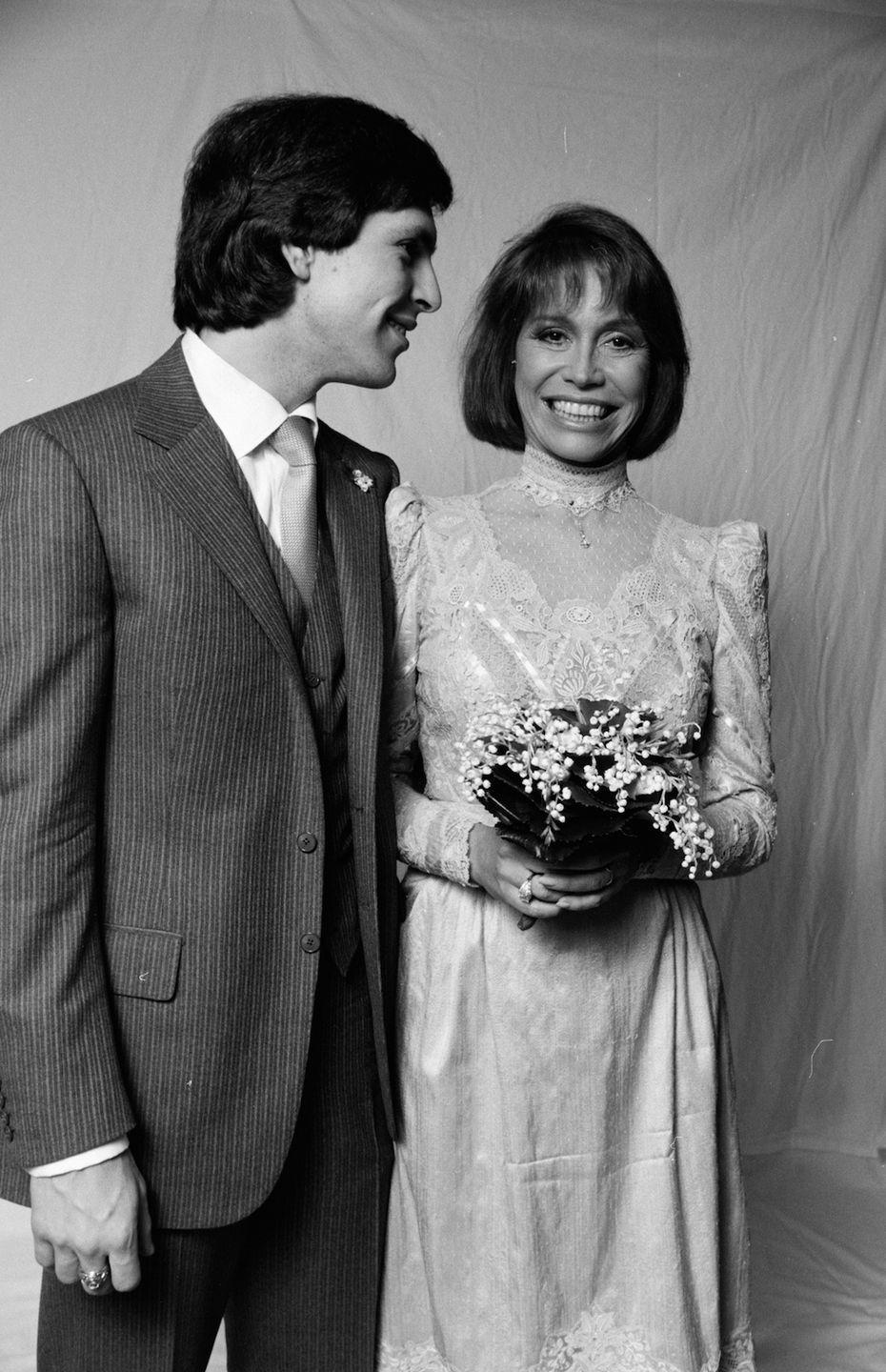 """<p>Mary Tyler Moore chose a more subdued version of an on-trend '80s look: Gathered sleeves and a high lace neckline. </p><p><a href=""""http://www.goodhousekeeping.com/beauty/fashion/a33719/wedding-dress-trends-through-the-years/"""" rel=""""nofollow noopener"""" target=""""_blank"""" data-ylk=""""slk:See the evolution of the wedding dress »"""" class=""""link rapid-noclick-resp""""><em>See the evolution of the wedding dress »</em></a><br></p>"""