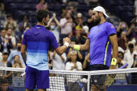 Novak Djokovic, left, of Serbia, shakes hands with Matteo Berrettini, of Italy, after Djokovic's win during the quarterfinals of the U.S. Open tennis tournament Thursday, Sept. 9, 2021, in New York. (AP Photo/Frank Franklin II)