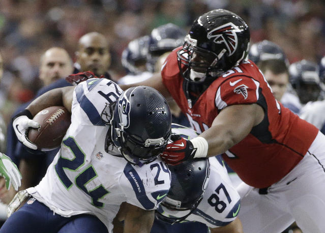 Seattle Seahawks running back Marshawn Lynch (24) is stopped by Atlanta Falcons defensive tackle Corey Peters (91) during the first half of an NFL football game, Sunday, Nov. 10, 2013, in Atlanta. (AP Photo/David Goldman)