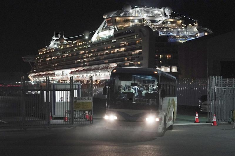 Buses carrying passengers from the quarantined Diamond Princess cruise ship leave a port in Yokohama (AP)