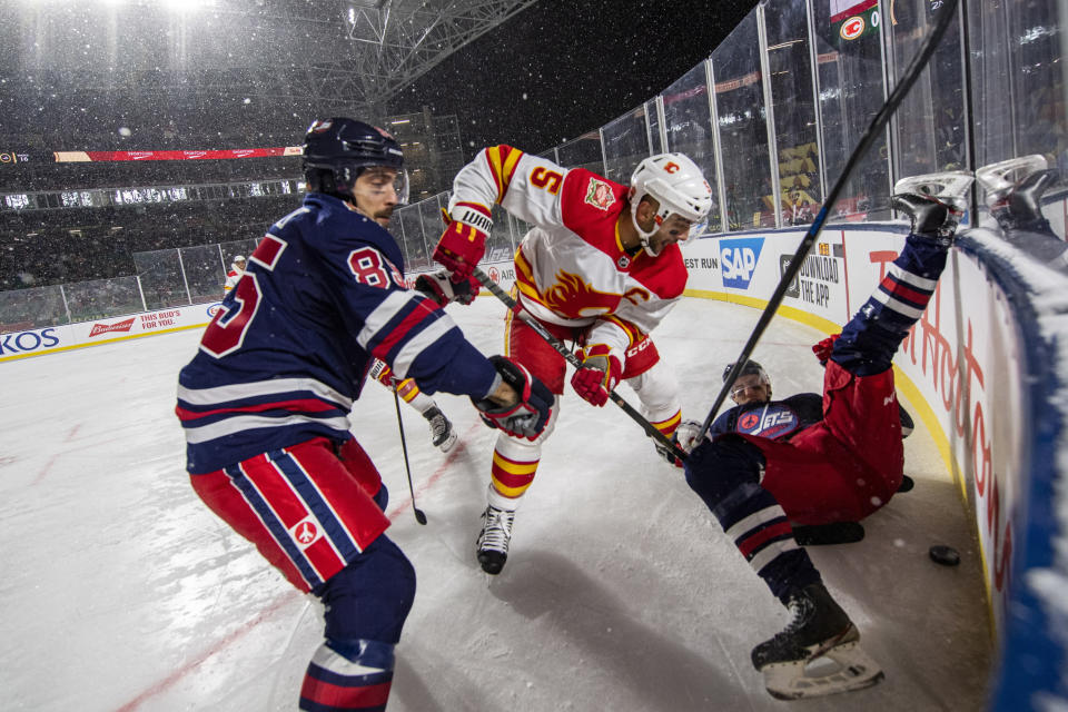 Calgary Flames' Mark Giordano (5) battles for the puck in the corner with Winnipeg Jets' Mathieu Perreault (85), left, and David Gustafsson (19) during the second period of an NHL Heritage Classic outdoor hockey game in Regina, Canada, Saturday, Oct. 26, 2019. (Liam Richards/The Canadian Press via AP)