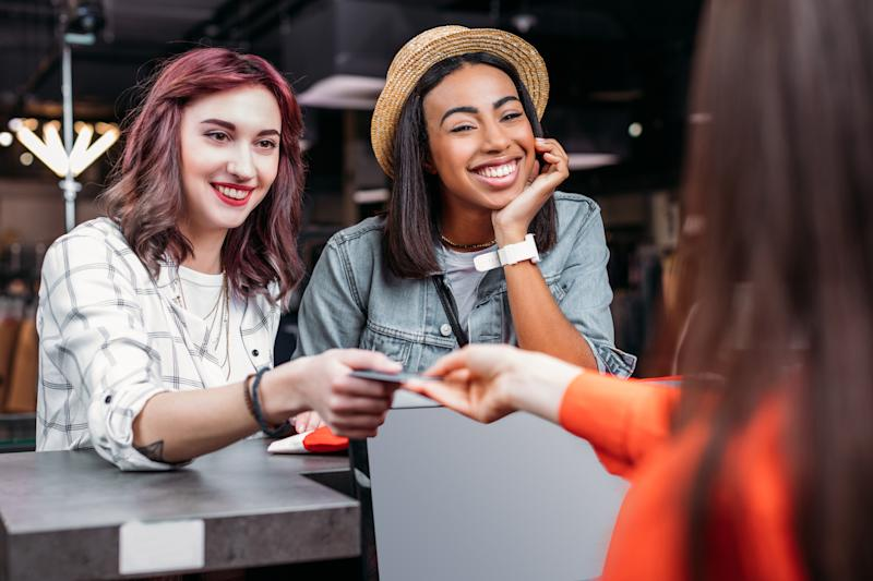 Two young women paying for purchases with a credit card.