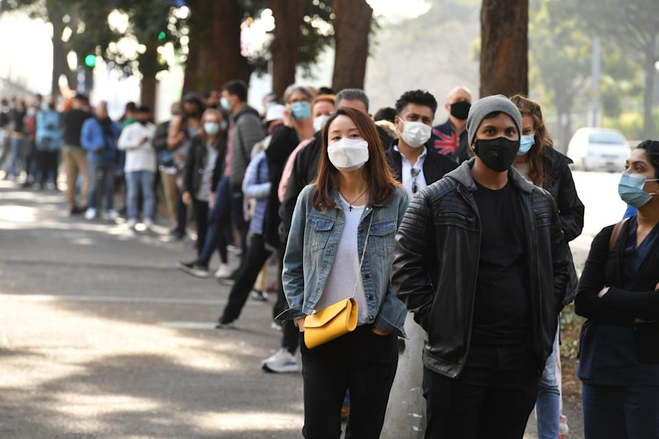 People are seen queued to receive their vaccination at the NSW Vaccine Centre at Homebush Olympic Park in Sydney. Source: AAP
