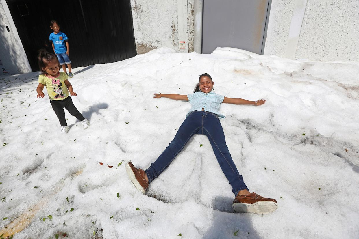 Residents play on hail, which affected some areas of Guadalajara, Mexico, on June 30. (Photo: Fernando Carranza/Reuters)