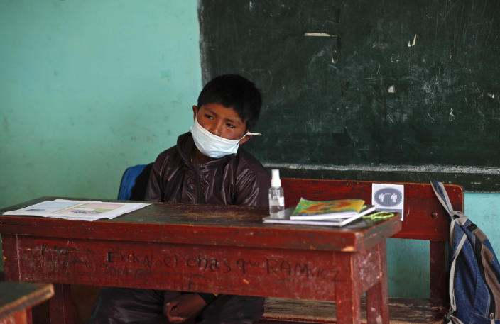 An Aymaran Indigenous student wears a mask and a new, protective uniform during the first week back to in-person classes amid the COVID-19 pandemic, near Jesus de Machaca, Bolivia, Thursday, Feb. 4, 2021. (AP Photo/Juan Karita)