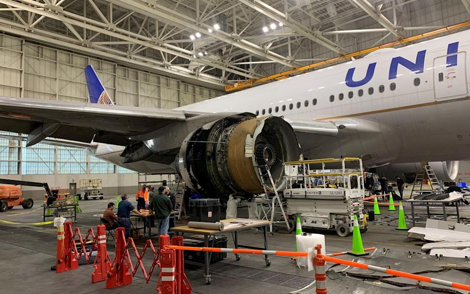 The damaged engine from the United Airlines Boeing 777 is inspected in a Denver hangar