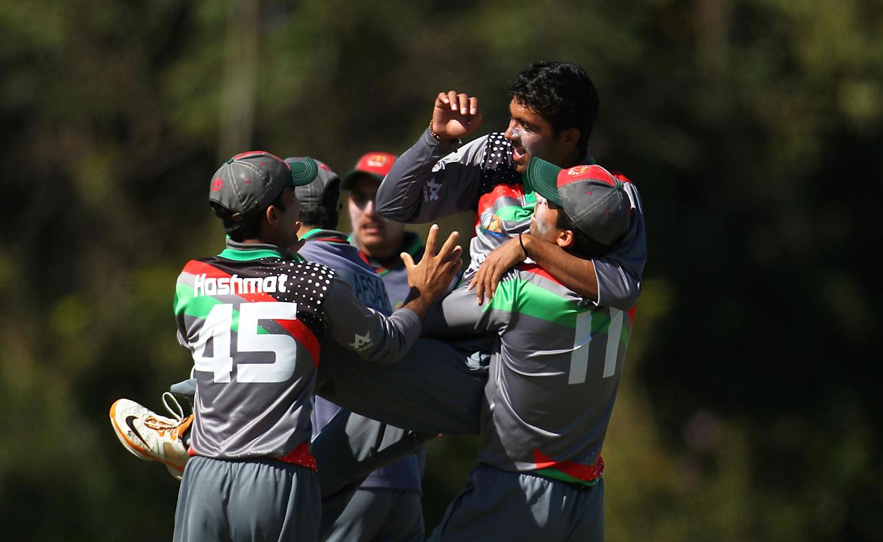 SUNSHINE COAST, AUSTRALIA - AUGUST 11:  Mohammad Yamin of Afghanistan is lifted and embraced by teams mates after the dismissal of Sami Aslam during the ICC U19 Cricket World Cup 2012 match between Pakistan and Afghanistan at John Blanck Oval on August 11, 2012 in Sunshine Coast, Australia.  (Photo by Graham Denholm-ICC/Getty Images)