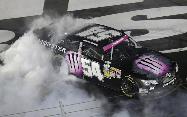 Kyle Busch does a burnout after winning the NASCAR Nationwide Series auto race at Charlotte Motor Speedway in Concord, N.C., Friday, Oct. 11, 2013. (AP Photo/Gerry Broome)