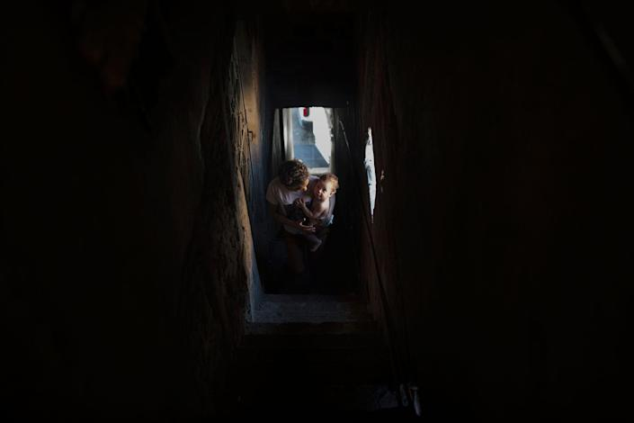 <p>Nayane walks up the stairs to her home in the Parque União favela, in the north of Rio de Janeiro, Brazil in August 2016. She holds Ana Sophia in her arms, her 10-month-old daughter. (Photo: Rafael Fabrés) </p>