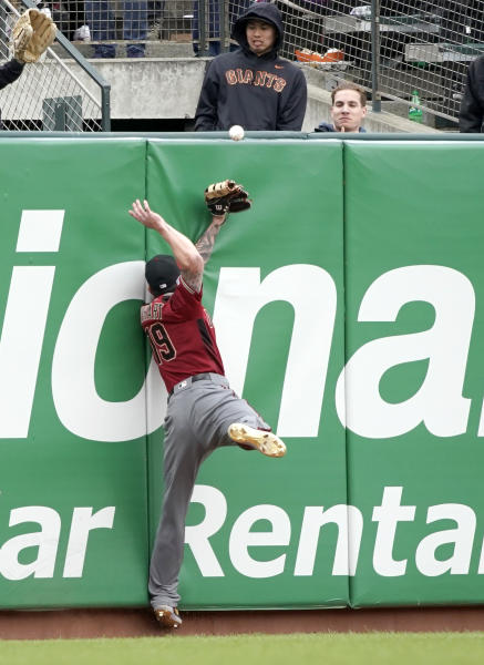 Arizona Diamondbacks left fielder Blake Swihart (19) cannot make the catch as he collides with the wall on a hit by San Francisco Giants' Stephen Vogt during the ninth inning of a baseball game in San Francisco, Sunday, May 26, 2019. (AP Photo/Tony Avelar)