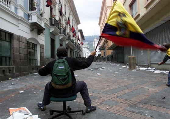 An Ecuadoran waves a national flag while sitting on a chair to face riot police guarding Carondolet Palace from thousands of protesters opposed to President Lucio Gutierrez, in Quito, April 20, 2005.