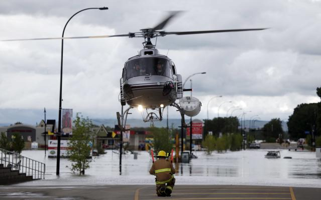A helicopter carrying evacuated residents lands on a road in High River, Alta., Thursday, June 20, 2013. Calgary city officials say as many as 100,000 people could be forced from their homes due to heavy flooding in western Canada, while mudslides have forced the closure of the Trans-Canada Highway around the mountain resort towns of Banff and Canmore. (AP Photo/The Canadian Press, Jeff McIntosh )