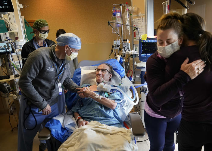 Dr. Mark Sprenkle, left, shakes hands with John Grubb as Grubb's wife Kelly, second from right, says goodbye to other HCMC caregivers before Grubb was discharged from HCMC Monday, May 3, 2021 in Minneapolis. Grubb, of St. Michael, was discharged from HCMC after 81 days on the ECMO heart-lung bypass machine. ECMO has been the treatment of last resort in COVID-19 care, saving 50% of people when used globally, but has been a critical tool when doctors run out of options for severely ill patients. (David Joles/Star Tribune via AP)