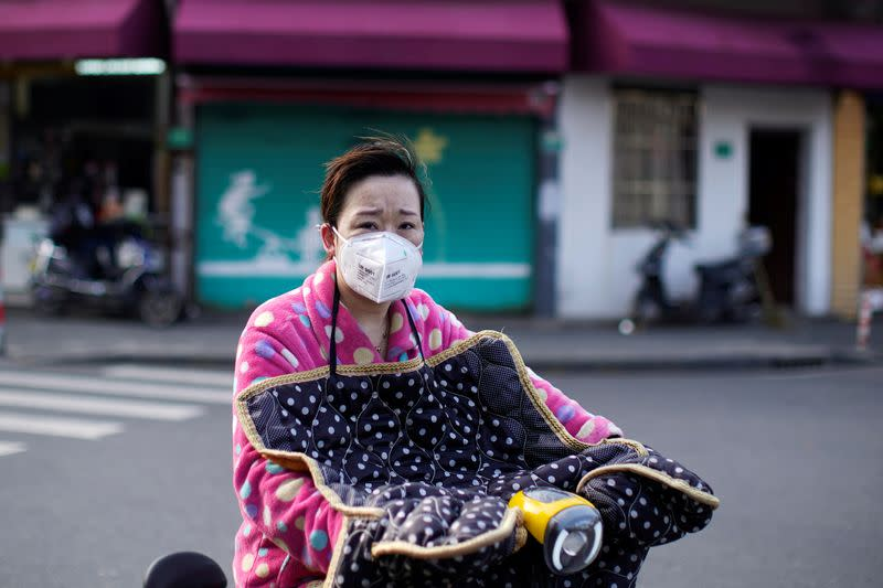 A woman wearing a mask is seen in downtown Shanghai