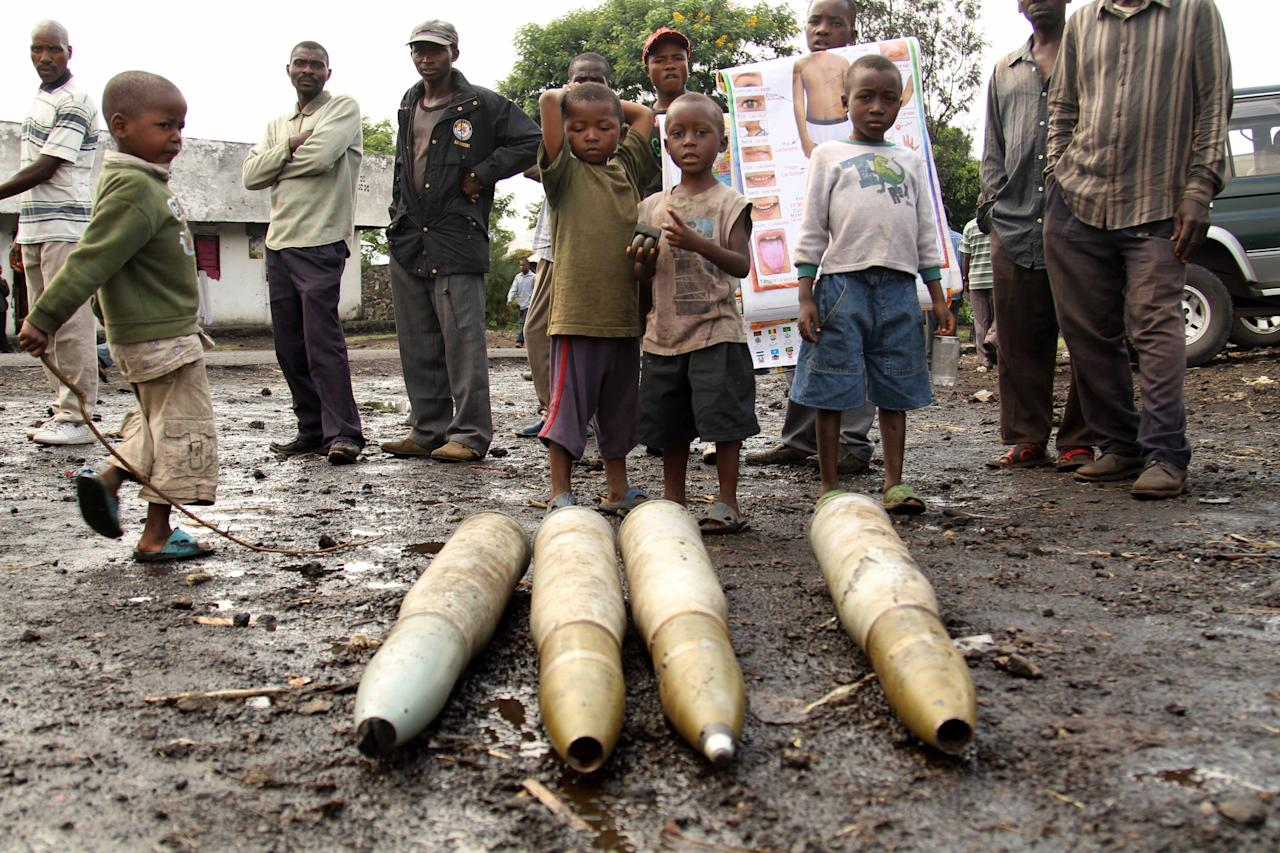 Congolese citizens look at tank shells lying next to the roadside, left behind by retreating government troops as they fled an assault by M23 rebels, in eastern Congo, Wednesday, Nov. 21, 2012. Thousands of Congolese soldiers and policemen defected to the M23 rebels Wednesday, as rebel leaders vowed to take control of all Congo, including the capital Kinshasa. The rebels organized a rally at Goma's Stadium of Volcanoes Wednesday after seizing control of the strategic city in eastern Congo Tuesday.(AP Photo/Marc Hofer)