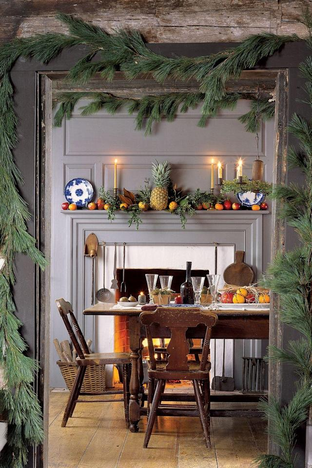 """<p>Evocative and soothing, candlelight creates the right ambience for the holidays. Lit candles are more than decorative objects, highlighting seasonal festivities and fostering a celebratory mood. Garlands around the door frame beckon guests into the room, and on the mantel sits a pineapple, an early-American symbol of hospitality.</p><p><a class=""""link rapid-noclick-resp"""" href=""""https://www.amazon.com/s/ref=nb_sb_noss_1?url=search-alias%3Daps&field-keywords=garlands&rh=i%3Aaps%2Ck%3Agarlands&tag=syn-yahoo-20&ascsubtag=%5Bartid%7C10050.g.644%5Bsrc%7Cyahoo-us"""" rel=""""nofollow noopener"""" target=""""_blank"""" data-ylk=""""slk:SHOP GARLAND"""">SHOP GARLAND</a></p>"""