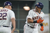 Houston Astros' Michael Brantley, right, celebrates with third base coach Omar Lopez (22) after hitting a three-run home run against the Chicago White Sox during the first inning of a baseball game Thursday, June 17, 2021, in Houston. (AP Photo/David J. Phillip)