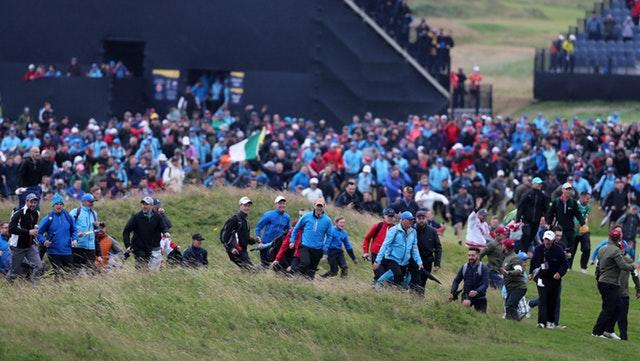 Fans rush on to the course