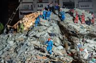Rescuers search for survivors among the rubble of a collapsed building after an earthquake in Turkey and Greece