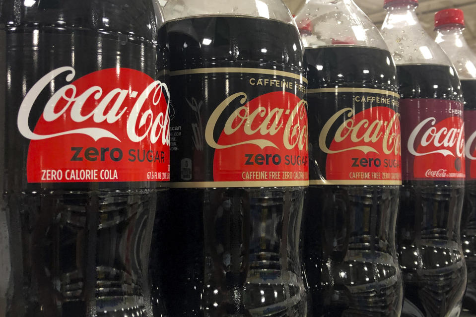Bottles of Coca-Cola products are shown, Tuesday, Oct. 20, 2020, at a store in Dania Beach, Fla. The Coca-Cola Co. said it saw gradual improvement in the third quarter, as it turned its focus to emerging leaner from the global pandemic. (AP Photo/Wilfredo Lee)
