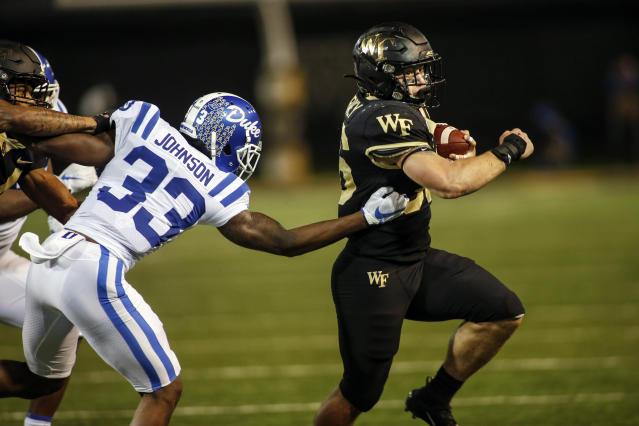 Wake Forest running back Cade Carney, right, breaks free from Duke cornerback Leonard Johnson as he runs for an 18-yard touchdown in the second half of an NCAA college football game in Winston-Salem, N.C., Saturday, Nov. 23, 2019. Wake Forest won 39-27. (AP Photo/Nell Redmond)