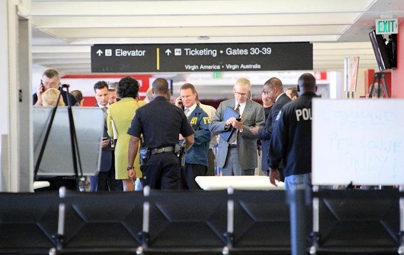 FILE - In this Nov. 1, 2013 file photo, federal and local investigators gather in Terminal 3 at Los Angeles International Airport where a gunman armed with a semi-automatic rifle opened fire, killing a Transportation Security Administration employee and wounding two other people. Two armed police officers, not seen in this photo, assigned to guard the terminal, left for breaks without informing dispatchers as required minutes before the gunfire erupted. (AP Photo/Ringo H.W. Chiu, File)