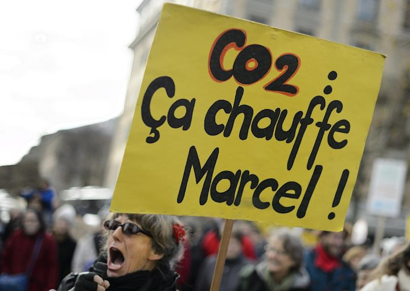 "A demonstrator holds a banner which reads ""CO2: it's getting hot Marcel!"" (AFP Photo/Fabrice Coffrini )"