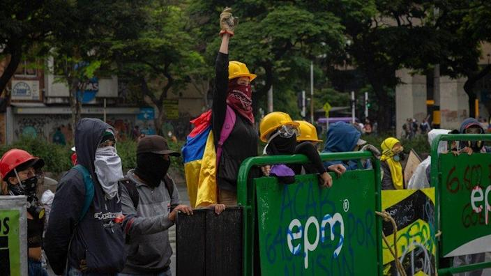 A woman raises her arm at a protest in Medellín on 18 May 2021