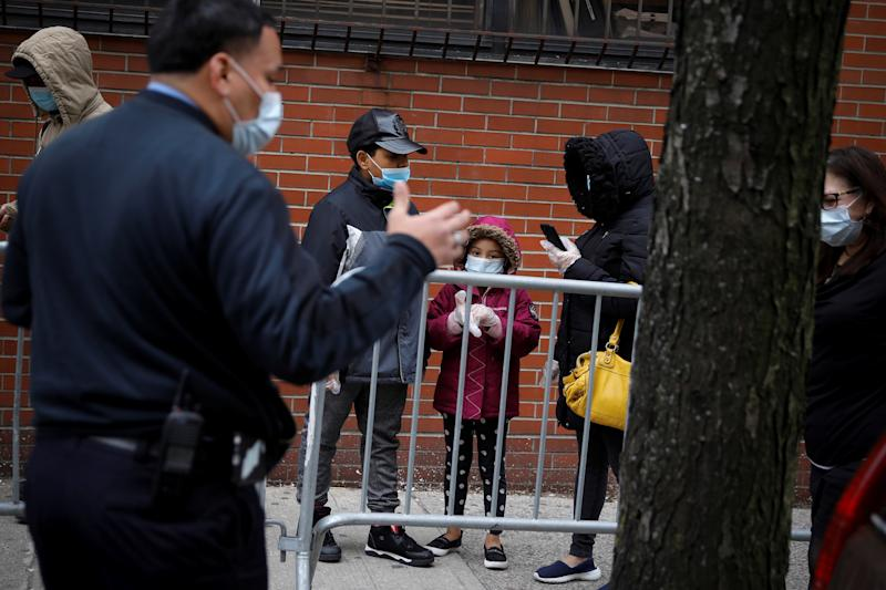 An official wearing a protective face mask speaks to people waiting in line outside NYC Health + Hospitals/Gotham Health Morrisania neighborhood health center, one of New York City's new walk-in COVID-19 testing centers, during the outbreak of the coronavirus disease (COVID-19) in the Bronx borough of New York City, New York, U.S., April 20, 2020. REUTERS/Mike Segar